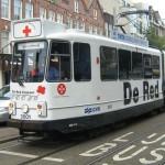 Rolstoel of scootmobiel tocht door Amsterdam met de Red Croser tram